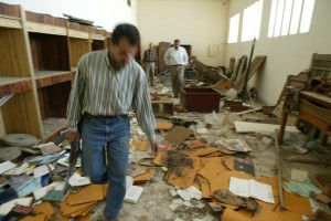 Iraqi guards walk in the ransacked and looted Iraq's largest archeological museum in Baghdad, 13 April 2003.