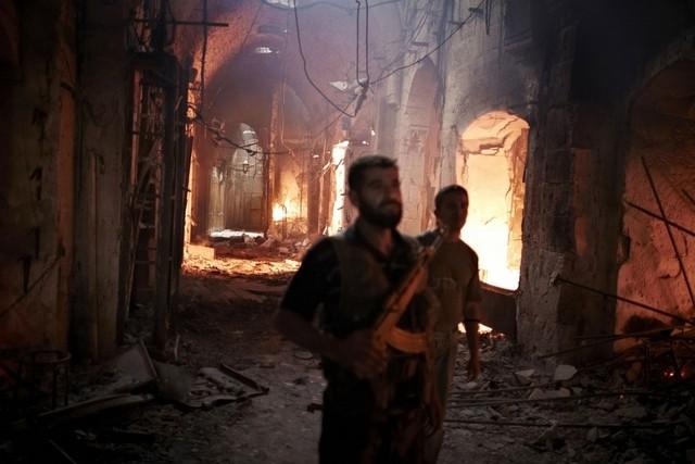 Two men walk through as a historic neighborhood burns during a military raid.