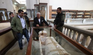 5 men stand arround a mummy coffin that had been looted.