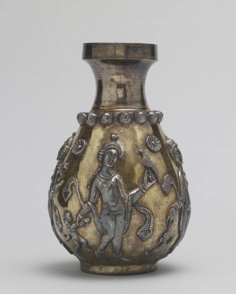 A bottle with sculptural figures of humans and animals, as well as floral details.
