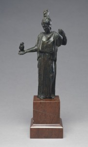 Bronze sculpture of a woman in a dress holding small owl.